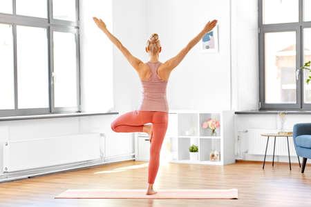 young woman doing yoga tree pose at home