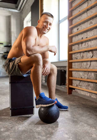 happy smiling young man with medicine ball in gym