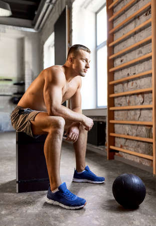 young man with medicine ball in gym