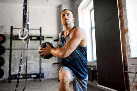 young man exercising with medicine ball in gym