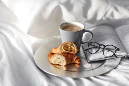 croissants, cup of coffee and book in bed at home Imagens