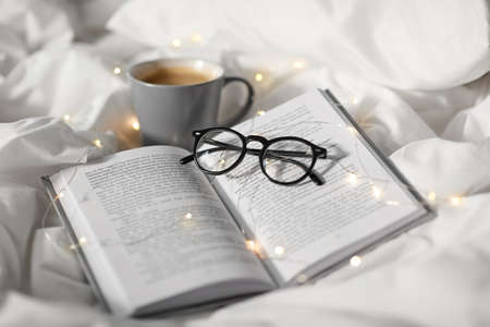 cup of coffee, book, glasses and garland in bed Imagens