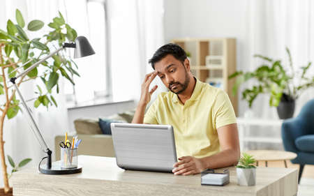 indian man with laptop working at home office