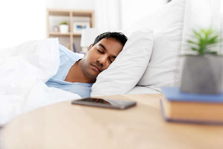indian man sleeping in bed at home Standard-Bild