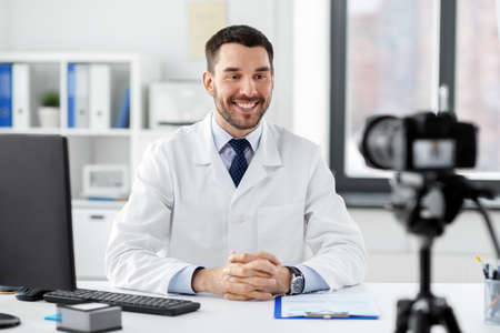 male doctor recording video blog at hospital