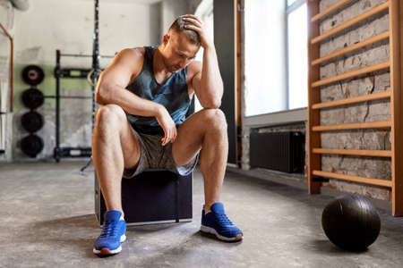 tired young man with medicine ball in gym