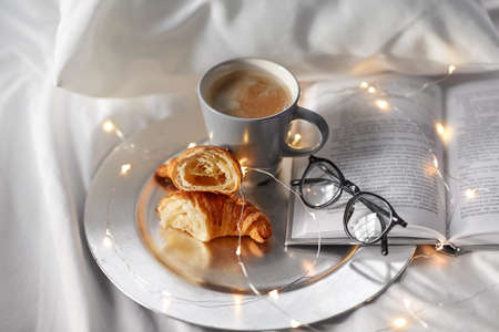 croissants, cup of coffee, book and glasses in bed