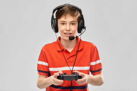 boy in headphones with gamepad playing video game