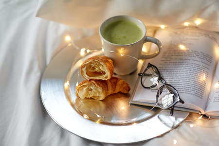 croissants, matcha tea, book and glasses in bed