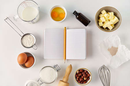 recipe book and cooking ingredients on table