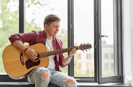 young man playing guitar sitting on windowsill
