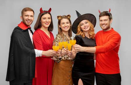 happy friends in halloween costumes over grey