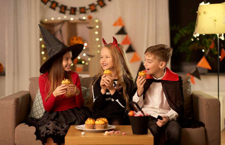 kids in halloween costumes eating cupcakes at home