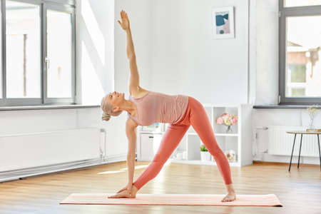 young woman doing yoga triangle pose at home