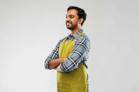 happy indian male gardener or farmer in apron