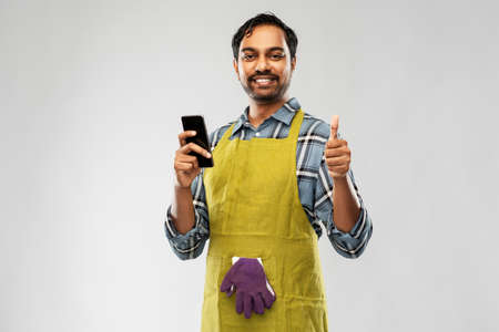 indian male gardener or farmer with smartphone