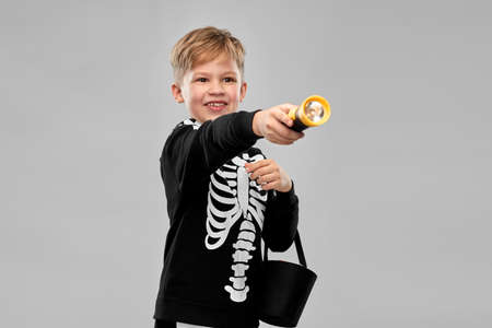 boy with candies and flashlight on halloween