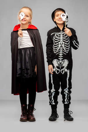 children in halloween costumes with party props