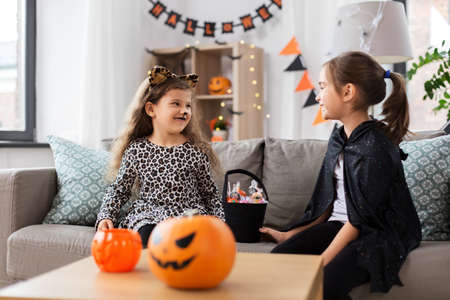 girls in halloween costumes with candies at home 스톡 콘텐츠 - 154174928