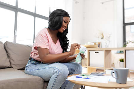 african american woman counting money at home Stock Photo