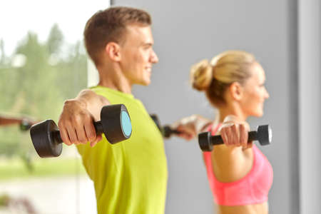close up of smiling woman with dumbbell in gym