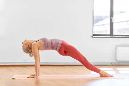 young woman doing yoga upward plank pose at studio