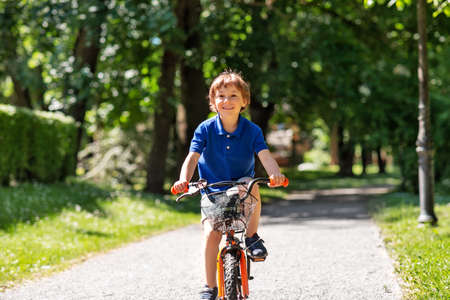 happy little boy riding bicycle at summer park Stockfoto