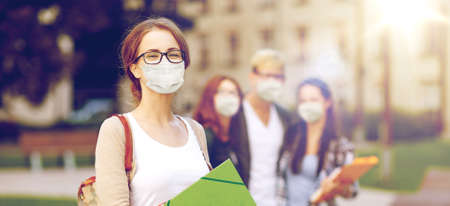 teenage student girl in mask with school friends Imagens