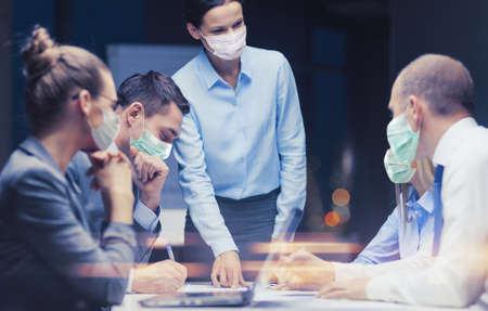 female boss in mask with business team at office