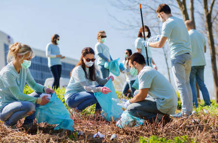 volunteers in masks with bags cleaning outdoors