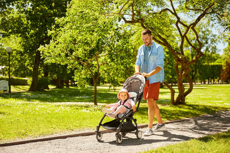 happy father with child in stroller at summer park