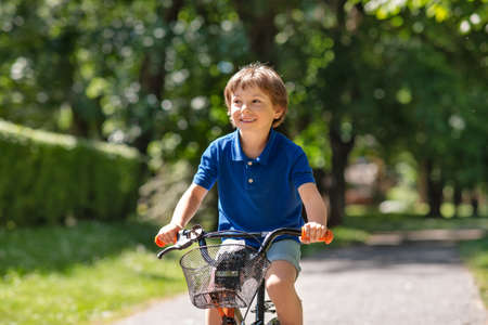 happy little boy riding bicycle at summer park Stock Photo