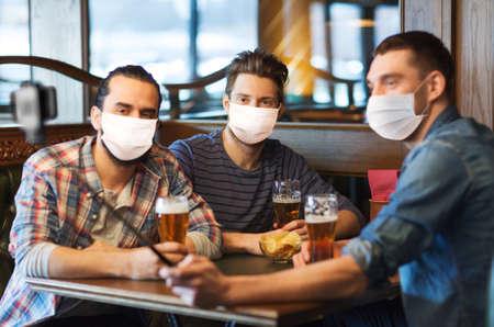men in masks take selfie and drink beer at bar Standard-Bild