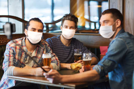 men in masks take selfie and drink beer at bar Stock Photo