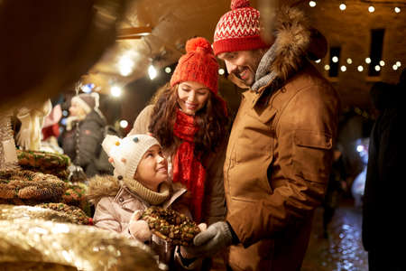 happy family buing wreath at christmas market