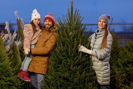 happy family choosing christmas tree at market