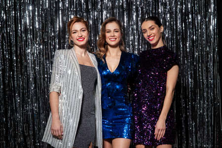 happy women hugging at party over silver tinsel
