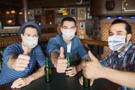 male friends in masks drinking beer at bar or pub