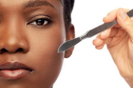 face of african american woman and scalpel knife Standard-Bild