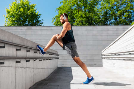 young man in headphones stretching leg outdoors