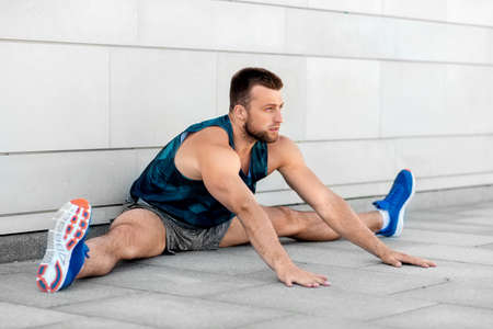 man doing sports and stretching outdoors