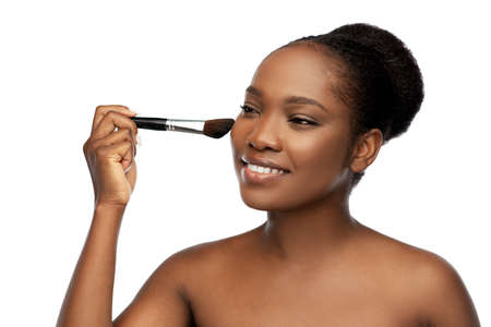 woman with make up brush applying blush to face