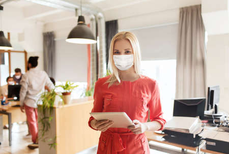 female office worker in mask with tablet pc