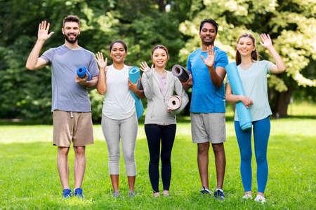 happy people with yoga mats waving hands at park Banco de Imagens