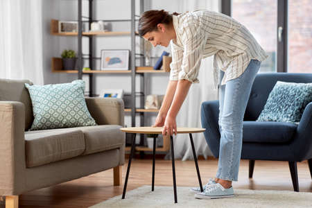 woman placing coffee table next to sofa at home