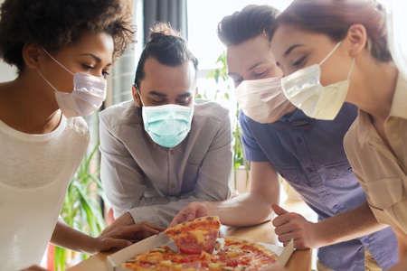 business team eating in masks pizza at office
