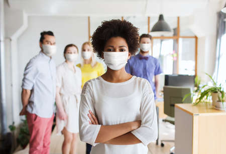 woman in mask over creative team at office