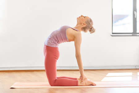 young woman doing yoga camel pose at studio