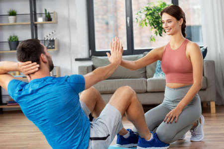 man with personal trainer doing sit ups at home Banco de Imagens