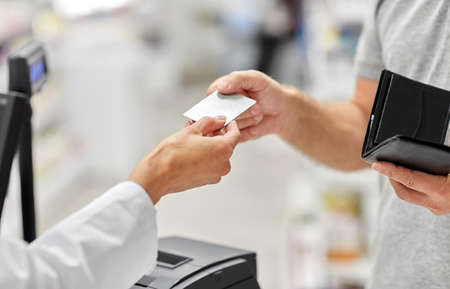 close up of hand giving bank card to pharmacist Foto de archivo